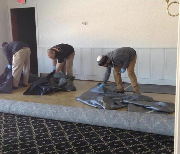 three worker picking up a black plastic cover (bag). Concept cleaning after water damage